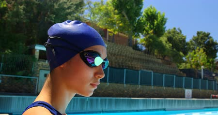 plavec : Female swimmer standing near poolside. Woman looking at camera 4k