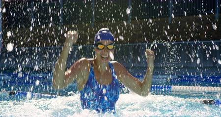 čepice : Excited female swimmer cheering in swimming pool. Happy female swimmer arms up in water 4k