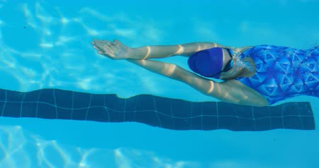 nadador : Young female swimmer swimming underwater. Female swimmer practicing backstroke 4k