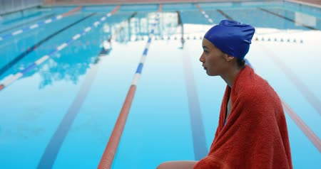 čepice : Female swimmer sitting near swimming pool. Thoughtful female swimmer wrapped in towel 4k
