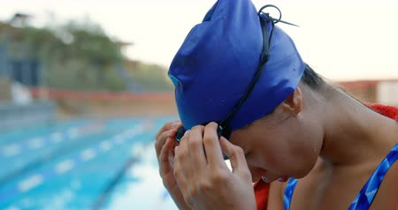nadador : Female swimmer removing swim goggle. Woman sitting near poolside 4k Stock Footage