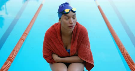 nadador : Female swimmer sitting near swimming pool. Thoughtful female swimmer wrapped in towel 4k