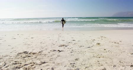 sports suit : Male surfer walking with surfboard at beach. Male surfer holding surfboard 4k
