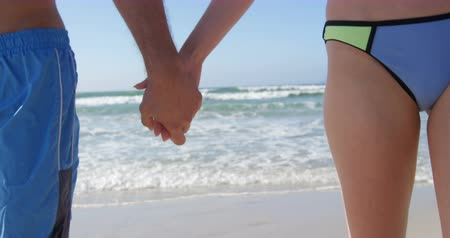 mid section : Romantic couple walking with hand in hand at beach. Mid section of couple holding hands 4k Stock Footage