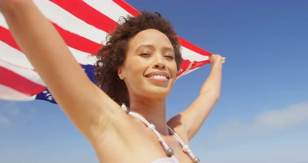 identità : Woman standing by the sea with a waving American flag.at beach. Woman holding an American flag 4k