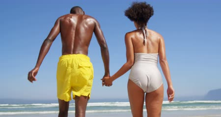романтический : Romantic couple running hand in hand at beach. Rear view of couple holding hands at beach 4k