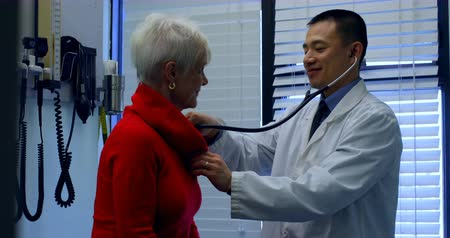 důchodce : Side view of young Asian male doctor examining a senior patient in the clinic. Young Asian male doctor interacting with senior patient 4k Dostupné videozáznamy