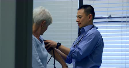 gauge : Side view of young Asian male doctor checking blood pressure of senior patient in the clinic. Young Asian male doctor examining a senior patient 4k
