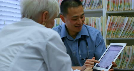 důchodce : Young Asian male doctor and senior patient discussing over digital tablet in the clinic. Young Asian male doctor and senior patient sitting at desk 4k