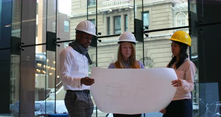 hard hat : Group of architects discussing over blueprint in office. Group of architects holding blueprint 4k