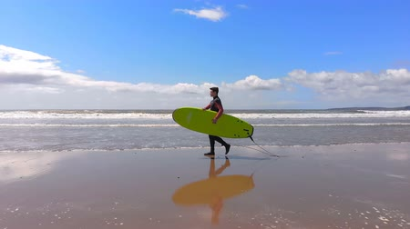 extreme weather : Male surfer walking with surfboard at beach on a sunny day. Male surfer holding surfboard 4k