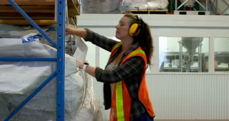 earmuffs : Side view of young caucasian female worker checking stock in factory. 4k Stock Footage