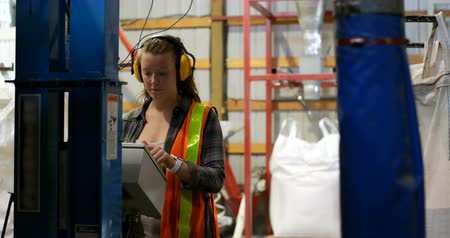 earmuffs : Front view of young caucasian female worker working in factory. Young caucasian female worker operating machine 4k Stock Footage
