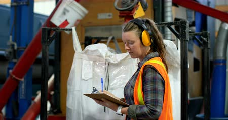 earmuffs : Side view of young caucasian female worker checking stocks in factory. Young caucasian female worker writing on notepad 4k Stock Footage