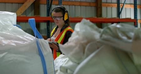 earmuffs : Front view of caucasian female worker working on digital tablet in warehouse. High rack with packed goods on foreground 4k