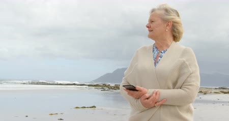 desviando o olhar : Front view of old caucasian senior woman using mobile phone at beach. She is smiling and looking away 4k Stock Footage