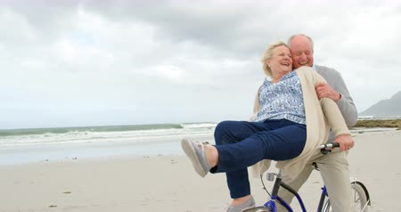 70年代 : Front view of old caucasian senior couple sitting on a bicycle at beach. They are smiling and having fun 4k 動画素材