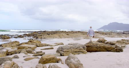 comprimento total : Rear view of old caucasian senior man walking over rocks at beach. Beautiful sky and calm sea in the background 4k