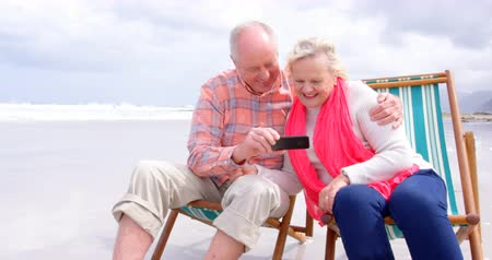 active ageing : Front view of old caucasian senior couple using mobile phone and sitting on sunlounger a beach. They are smiling and looking at mobile phone 4k