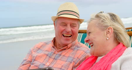 уик энд : Front view of old caucasian senior couple using digital tablet and sitting on sunlounger a beach. They are smiling looking at each other 4k