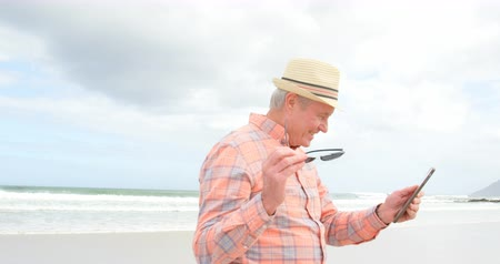 anni settanta : Side view of old caucasian senior man using digital tablet at beach. Old caucasian senior man smiling and looking at digital tablet 4k