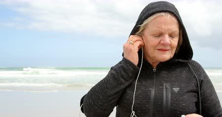 capuchon : Front view of old caucasian senior woman listening music on earphones at beach. She is smiling and looking away 4k