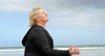 closed : Side view of old caucasian woman meditating at beach. Beautiful sea and calm sea in the background 4k Stock Footage