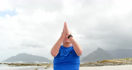 důchodce : Front view of old caucasian man meditating at beach. Beautiful sea and calm sea in the background 4k Dostupné videozáznamy