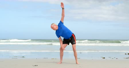 gepensioneerd : Front view of old caucasian man exercising at beach. Beautiful sky and calm sea in the background 4k