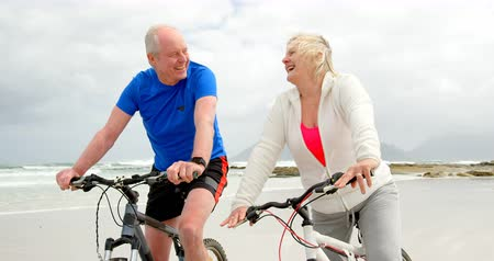 семидесятые годы : Front view of old caucasian couple riding bicycle at beach. Old caucasian couple smiling and looking at each other 4k Стоковые видеозаписи