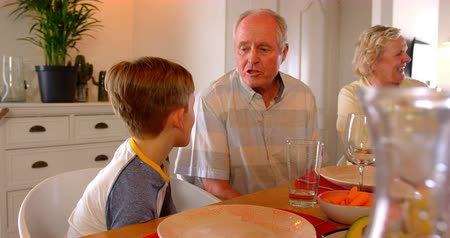 clasped : Caucasian Grandfather interacting with his grandson at dining table in a comfortable home. They are sitting together at dining table 4k