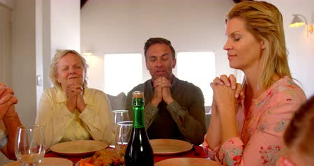 clasped : Front view of caucasian family praying together at dinning table in a comfortable home. They are sitting with eye closed and hands clasped 4k