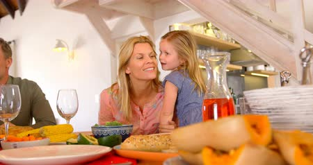 clasped : Front view of caucasian mother interacting with her daughter at dining table in a comfortable home. They are sitting together at dining table 4k