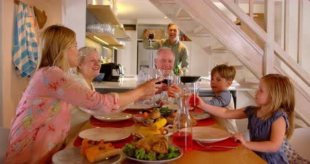 dede : Caucasian multi-generation family toasting glasses of drinks on dining table at home. Happy multi-generation family sitting at dining table 4k Stok Video