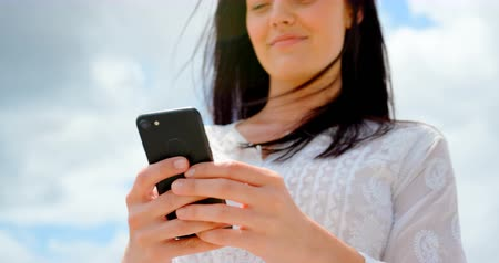 comprimento total : Low angle view of young caucasian woman using mobile phone at beach. She is smiling and looking away 4k