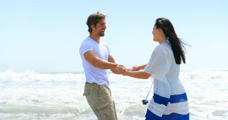 comprimento total : Slow motion of happy young caucasian couple hand in hand at beach 4k