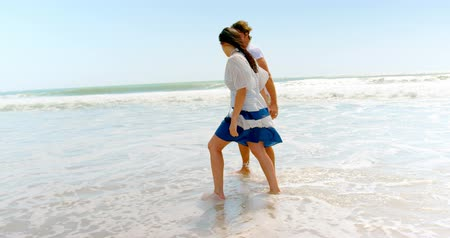 gömleksiz : Side view of young caucasian couple walking with hand in hand by the ocean 4k