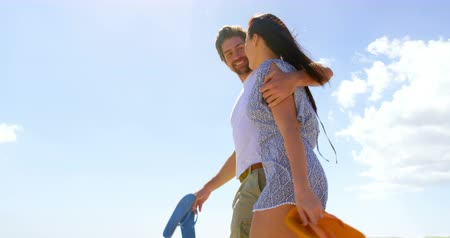 terlik : Low angle of young caucasian couple walking at beach on a sunny day. They are interacting with each other 4k
