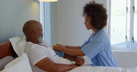 sphygmomanometer : Mixed race female doctor checking blood pressure of mature man at home. Female doctor and mature man interacting with each other 4k Stock Footage