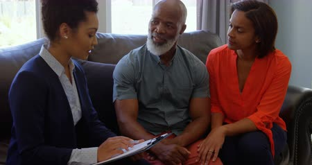 confirmação : Mixed race female real estate agent discussing over property with mature couple at home. They are dealing in home ownership 4k