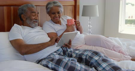 yatak kıyafeti : Side view of mature couple making video call on digital tablet at home. They are gesturing and drinking coffee 4k