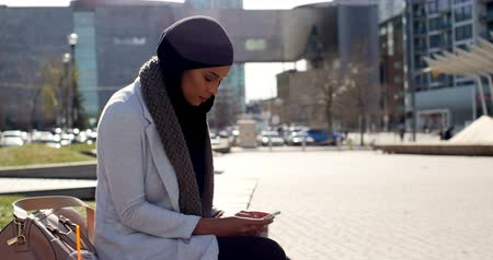 descartável : Side view of young Asian woman in hijab using mobile phone in the city. Young Asian woman drinking cold drink 4k