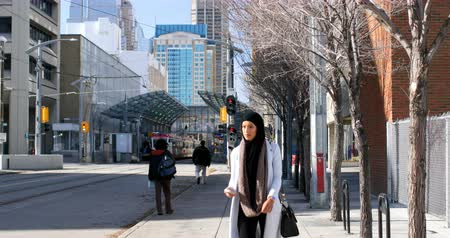 purse : Front view of young Asian woman in hijab using mobile phone in the city. Young Asian woman walking on sidewalk in the city 4k