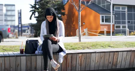 comprimento total : Front view of young Asian woman in hijab using digital tablet in the city. Young Asian woman drinking cold drink 4k Stock Footage