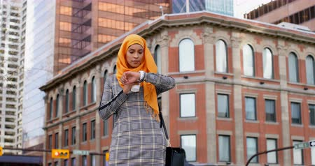 питьевой : Front view of young Asian woman in hijab standing in the city. Thoughtful young Asian woman checking time 4k Стоковые видеозаписи