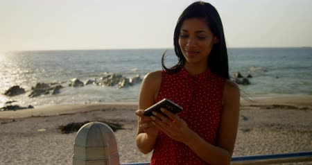comprimento total : mixed-race Woman clicking photo of sea with mobile phone. mixed-race Woman standing on promenade 4k