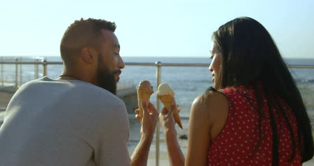 перила : Smiling mixed-race couple toasting each other with their ice cream cones. mixed-race Couple sitting on promenade 4k