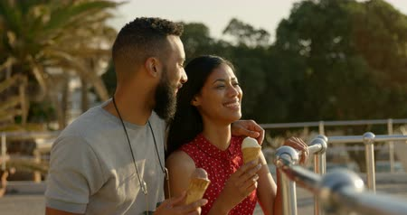 railing : Happy mixed-race couple standing with ice cream cones at promenade. mixed-race Couple looking at sea 4k