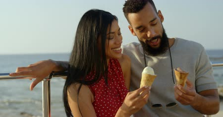 шишка : Happy mixed-race couple standing with ice cream cones at promenade. mixed-race Couple interacting with each other 4k