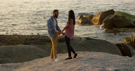 comprimento total : mixed-race Couple holding hands while standing on rock at beach. Romantic mixed-race couple standing at beach during sunset 4k Stock Footage